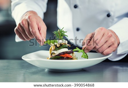 Chef in Restaurant garnishing vegetable dish, crop on hands, filtered image Royalty-Free Stock Photo #390054868