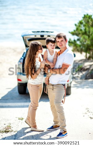 Man woman and child of three years old on the sea near the car of the jeep ready to travel #390092521