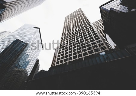 Cityscape view with business buildings with contemporary architecture in metropolitan city in day. High-rise modern skyscrapers in big town against grey sky #390165394