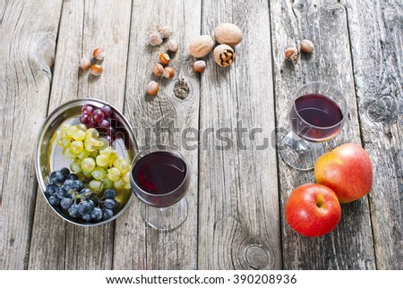 autumn still life with wine, apples, grapes, nuts on old wooden #390208936