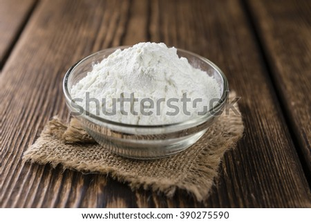 Portion of Milk Powder (close-up shot) on wooden background #390275590