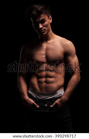 portrait of fit, muscular, topless man with hands in pockets, looking at the camera in dark studio background #390298717