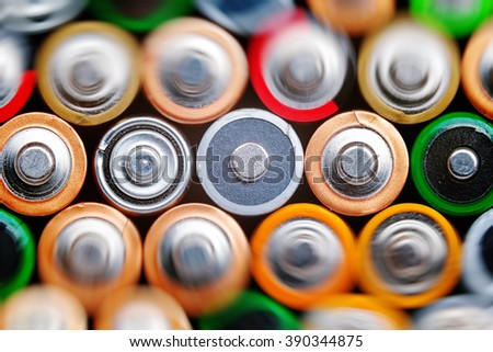 Several batteries are next to each other. Many aa batteries. Energy abstract background of colorful batteries. Close up top view on rows of selection of AA batteries. Alkaline battery aa size. #390344875
