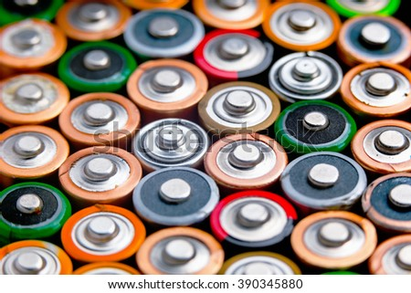 Energy abstract background of colorful batteries. Close up top view on rows of selection of AA batteries. Alkaline battery aa size. Several batteries are next to each other. Many aa batteries. #390345880