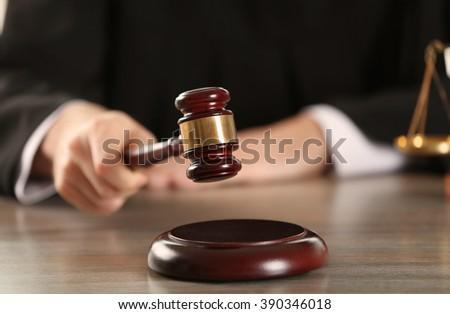 Judge hitting gavel at wooden table closeup