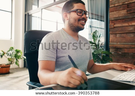 Happy young male designer working on graphics tablet using a stylus. Artist using new technology for editing his artwork. #390353788
