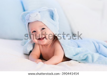 Baby boy wearing diaper and blue towel in white sunny bedroom. Newborn child relaxing in bed after bath or shower. Nursery for children. Textile and bedding for kids. New born kid with toy bear. Royalty-Free Stock Photo #390441454