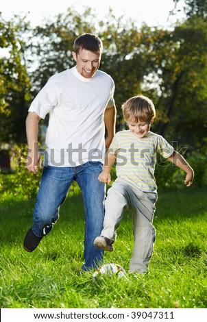 Cheerful father and son catch up with a football in park #39047311