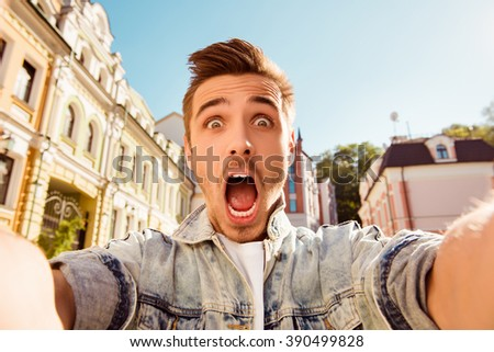 Handsome man making selfie and grimacing with opened mouth