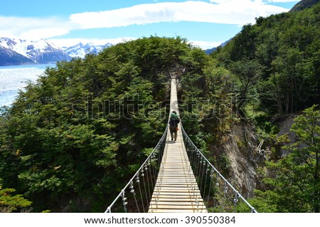 Backpacker cross a suspension bridge during a beautiful day in Torres del Paine National Park, Chile #390550384