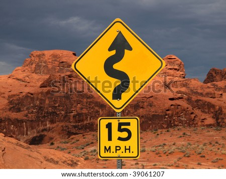 Curve sign against red desert cliffs at sunset. #39061207