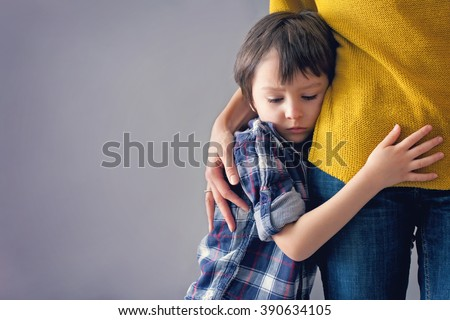 Sad little child, boy, hugging his mother at home, isolated image, copy space. Family concept #390634105