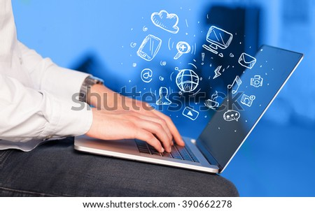 Hand writing on notebook computer with media icons and symbols comming out #390662278