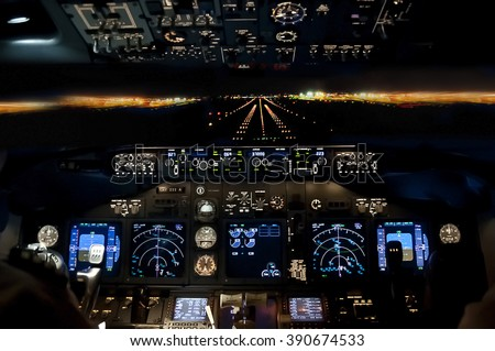 Final approach at night - landing of a jet airliner, view from the cockpit Royalty-Free Stock Photo #390674533