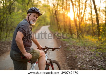 Senior man on his mountain bike outdoors (shallow DOF; color toned image) #390767470