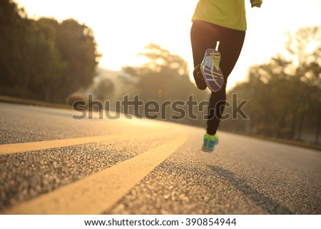 young fitness woman runner running on sunrise road #390854944