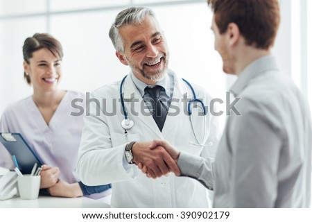 Smiling doctor at the clinic giving an handshake to his patient, healthcare and professionalism concept Royalty-Free Stock Photo #390902179
