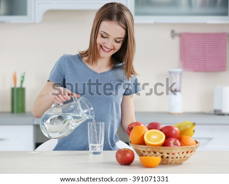 Young woman pouring water from jug into glass in the kitchen #391071331