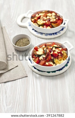 Vegetables (courgette, pepper, onion, tomatoes) and sausage bake with cheese #391267882