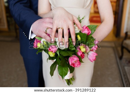 Hands of the groom and bride with rings and bridal bouquet #391289122