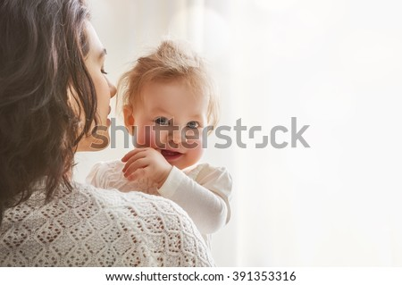happy loving family. mother playing with her baby in the bedroom. Royalty-Free Stock Photo #391353316