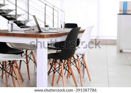 Modern office. Furniture set with table and chairs. Laptop on the table #391387786