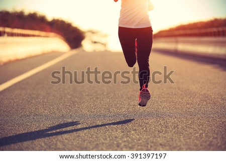 young fitness woman runner running on sunrise road #391397197