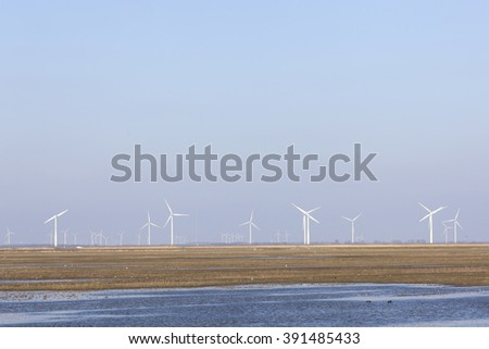 wind turbines and blue sky above Eempolder in the Netherlands with birds in meadow area #391485433