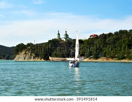 ABRAU DURSO, RUSSIA - AUGUST 27, 2015: Unidentified holidaymakers ride in a boat sailing on Lake Abrau #391491814