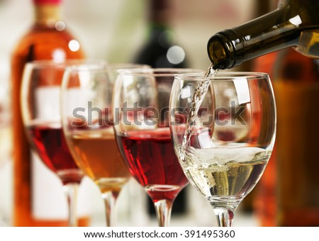 White wine pouring into glasses, closeup Royalty-Free Stock Photo #391495360