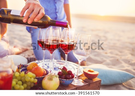 Group of happy friends having red wine on the beach. Sunset beach party #391561570