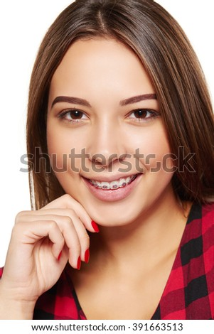 Closeup portrait of young teen female smiling with braces on her teeth #391663513