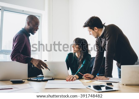 Multiracial business people working together connected with technological devices like tablet and notebook - teamwork, business, working concept #391748482