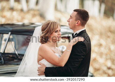 Stylish wedding couple, bride, groom kissing and hugging near retro car in autumn #392057290