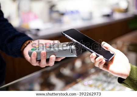 Female paying with NFC technology on smart phone #392262973