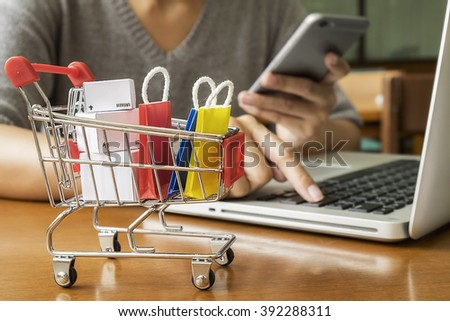 Internet online shopping concept with smartphone and shopping-cart.Vintage tone retro filter effect,soft focus(selective focus)  #392288311