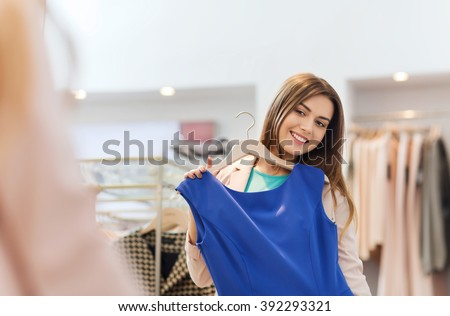 shopping, fashion, style and people concept - happy woman choosing clothes and looking to mirror in mall or clothing store #392293321