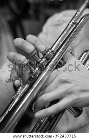Hands of the musician playing a trumpet closeup in black and white #392439715