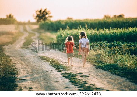 Two little sisters walking in a meadow on beautiful sunny day