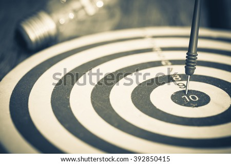 Smart goal setting, dart hit the center of dartboard with light bulb on background Royalty-Free Stock Photo #392850415
