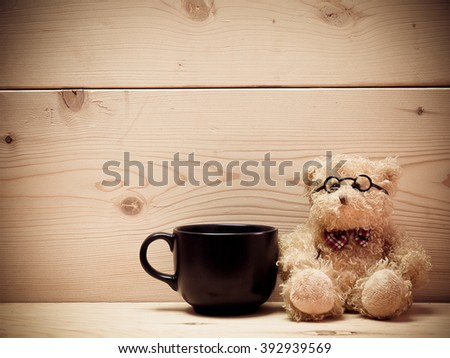 Coffee with teddy bear , The background is a brown wooden plate. (vintage) (picture with space for text)