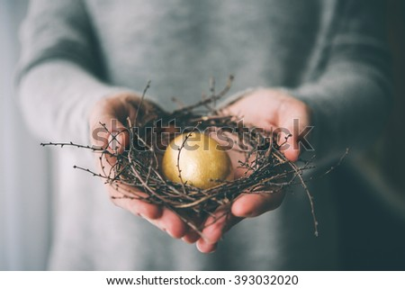 Hands holding golden egg in a small nest. Selective focus. Toned picture