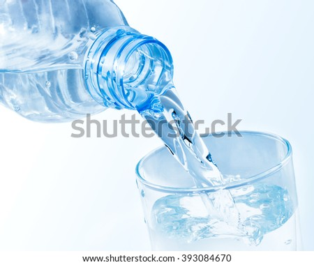 Pouring clean water from plastic bottle into a glass #393084670