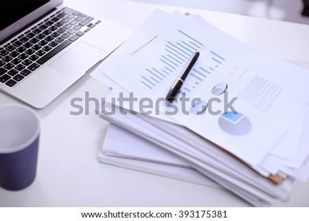 Office workplace with a laptop and financial documents on the light reflecting table #393175381