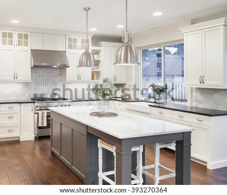 beautiful kitchen in luxury home with island, pendant lights, cabinets, and hardwood floors. tile back splash, stainless steel oven,range, and hood compliment the elegant features #393270364