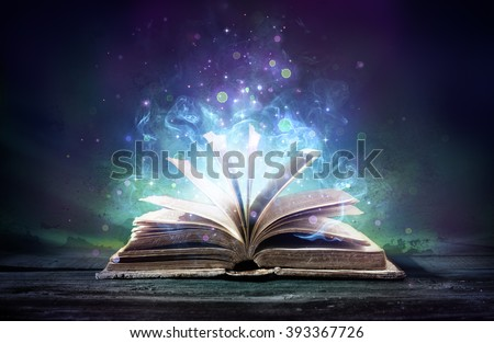 Bewitched Book With Magic Glows In The Darkness  Royalty-Free Stock Photo #393367726