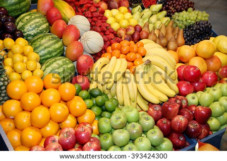 Freshly harvested collection of organic fruits as background. Close up of many colorful fruits on market stand. Big assortment of organic fruits on market  #393424300
