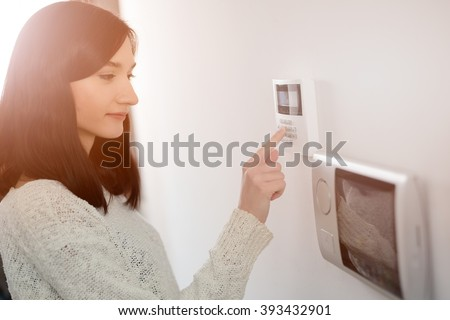Young brunette woman entering code on keypad of home security alarm. Video intercom next to alarm keypad. #393432901