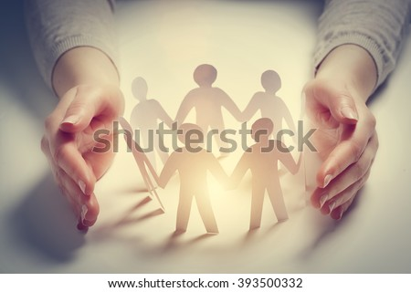 Paper people surrounded by hands in gesture of protection. Concept of insurance, social protection and support.  Royalty-Free Stock Photo #393500332