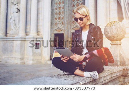 Hipster girl with trendy look is reading electronic book on portable touch pad, while is sitting outside the museum. Beautiful woman is watching movie on digital tablet, while relaxing after strolling #393507973